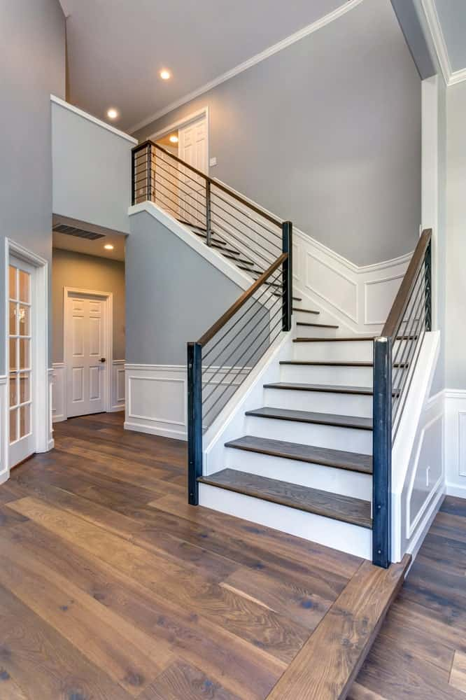 Stylish foyer featuring a hardwood flooring and gray walls together with the home's white details.