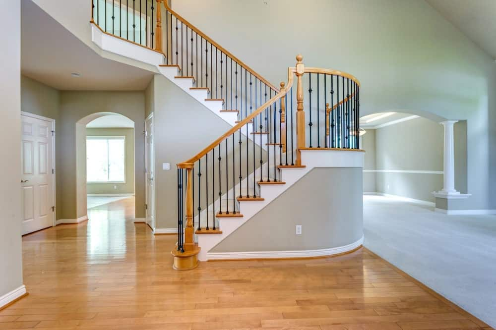 Still empty home featuring a hardwood flooring and gray walls. The staircase looks stunning.