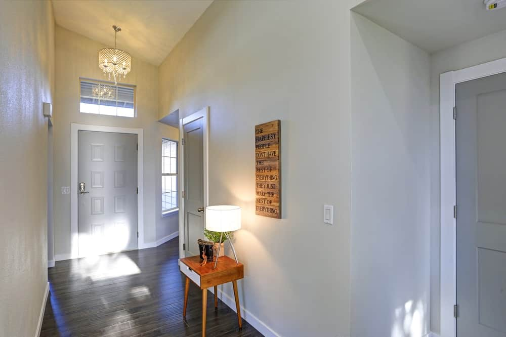 Small foyer featuring gray walls and hardwood flooring lighted by a small chandelier and a table lamp on the side.