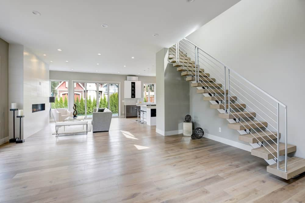 This large foyer boasts a matching grayish hardwood flooring and gray walls. The staircase looks beautiful together with the house's style.