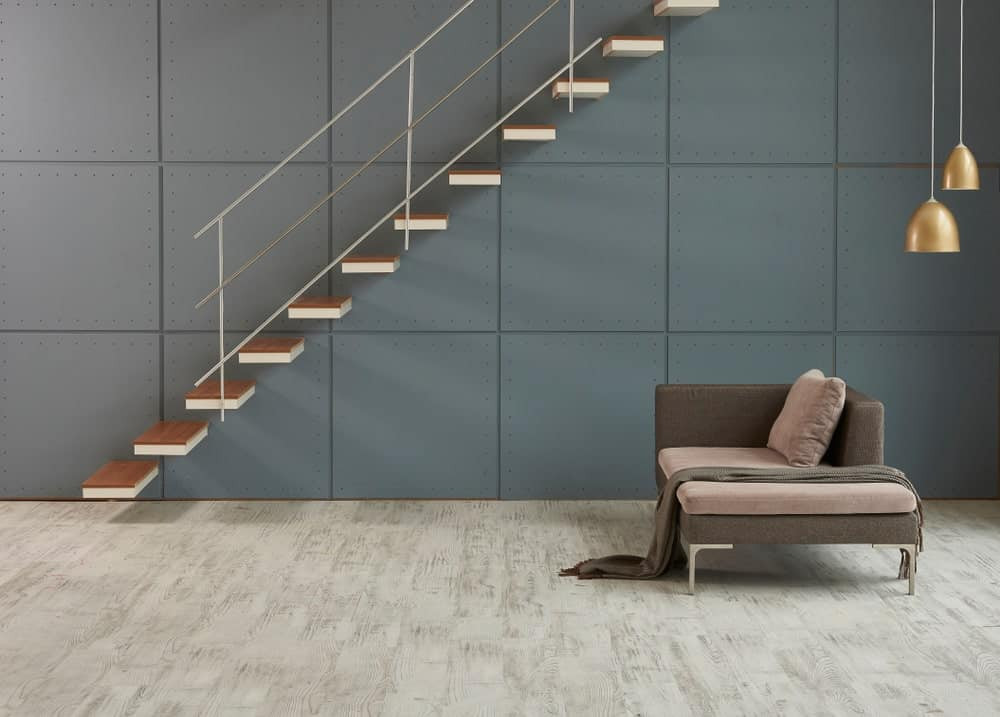 This foyer boasts a stylish flooring together with dark gray walls. The staircase looks so stunning.