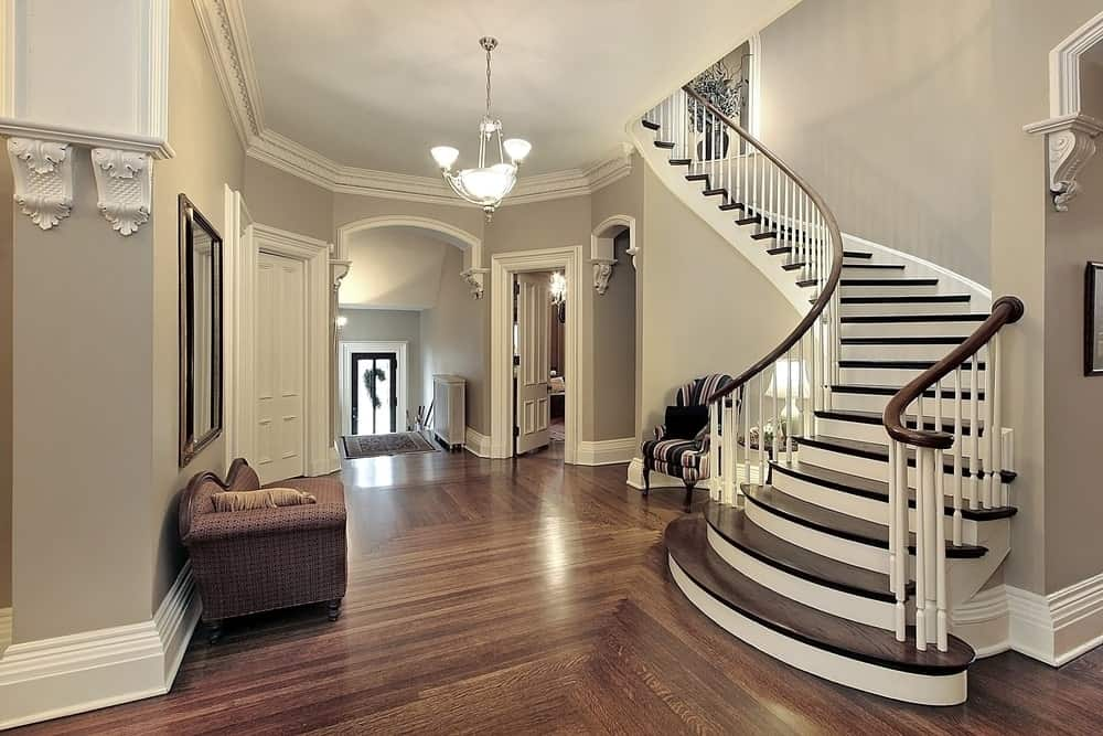 Classy foyer featuring a hardwood flooring, gray walls and white staircase, all lighted up by a pendant light, table lamp and wall lighting.