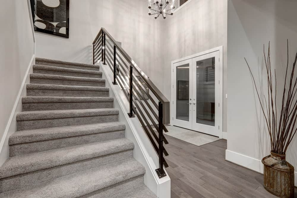 Classy foyer boasting a high ceiling with a jaw-dropping chandelier lighting up the home. The gray walls and staircase look so glamorous.