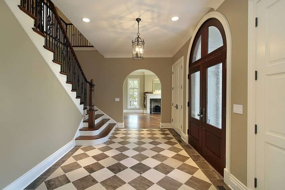 This classy foyer features a checker flooring, gray walls and vinyl staircase steps lighted by a stunning pendant light.