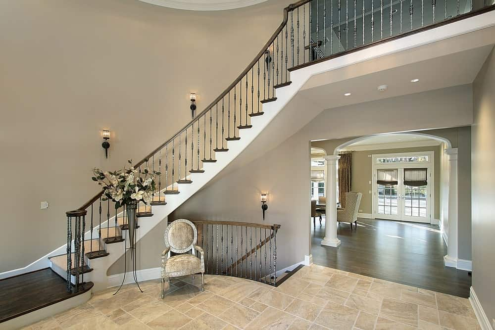 Large foyer featuring a glamorous staircase surrounded by gray walls and lighted by wall lights.