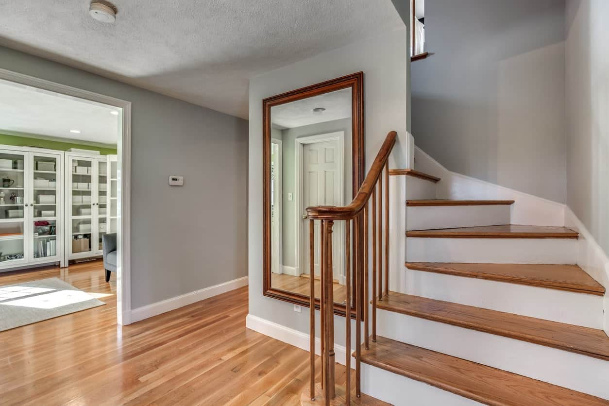 This foyer features a vinyl flooring surrounded by gray walls. The staircase's frame features white finish.