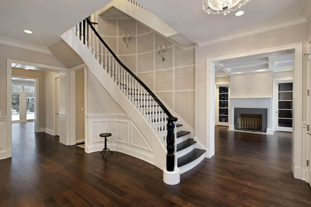 Large foyer featuring a hardwood flooring, white staircase and light gray walls lighted by wall lighting.