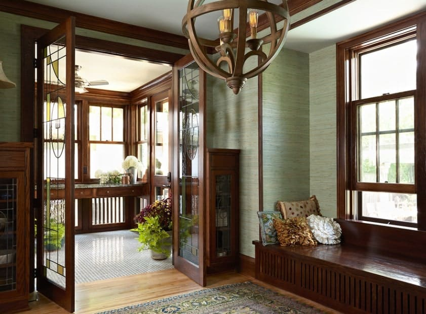 This foyer looks so lovely with its doors and windows, along with its bench seating and classy rug. The ceiling lighting is very attractive as well.