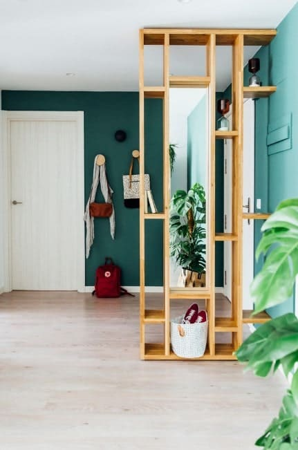 A modern foyer featuring green walls and hardwood flooring that look perfect together with each other.