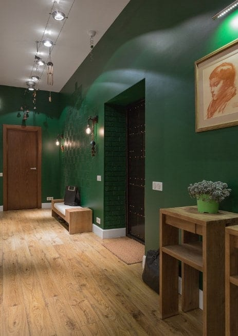 This home boasts green walls and hardwood flooring. The track lights and wall lights look absolutely stunning.
