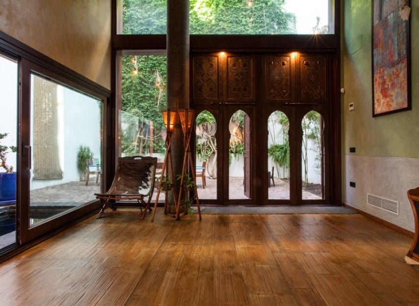 Large foyer with very attractive hardwood flooring and green walls. The doors look magnificent together with the lighting. The high ceiling adds elegance to the home's entry.