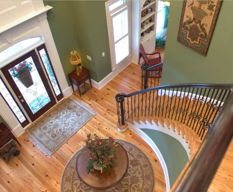 This foyer features green walls, a lovely pair of the rug on top of the hardwood flooring along with a classy staircase.