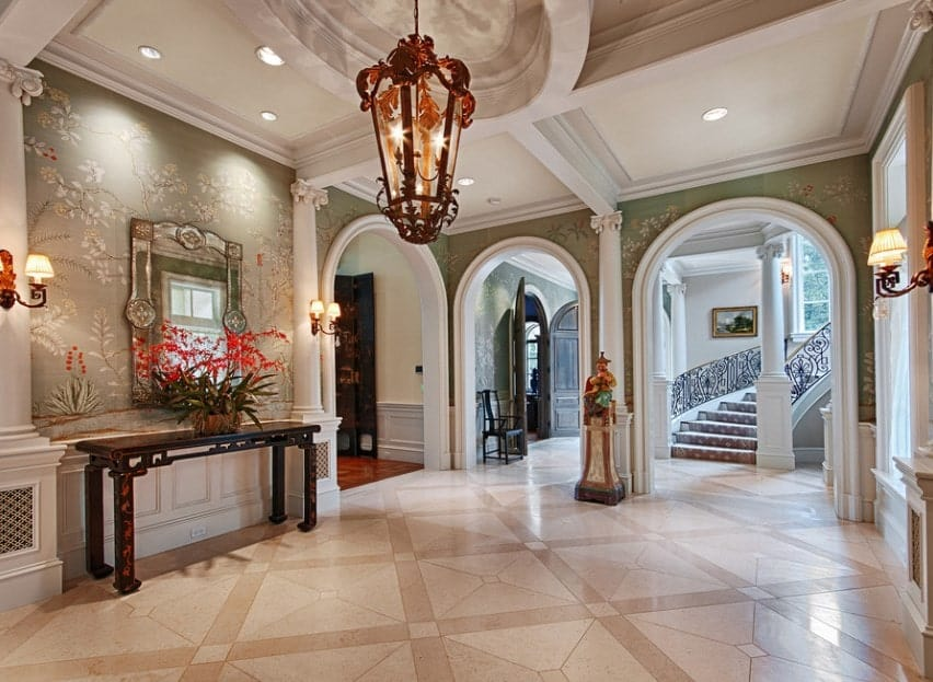 This mansion boasts a lovely foyer with classy tiles flooring and green walls along with a glamorous chandelier and wall lights.