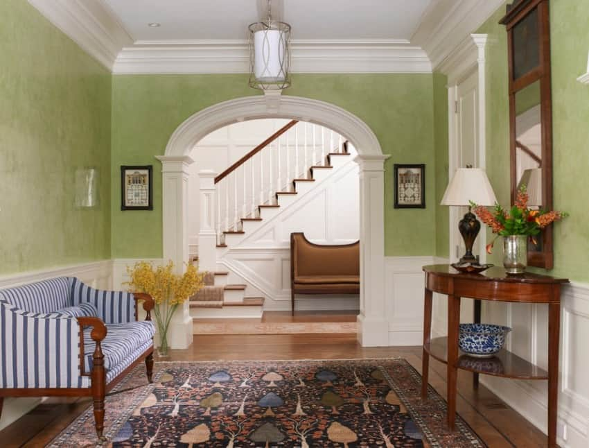 This foyer features a very charming rug to pair with the green walls with the white shade.