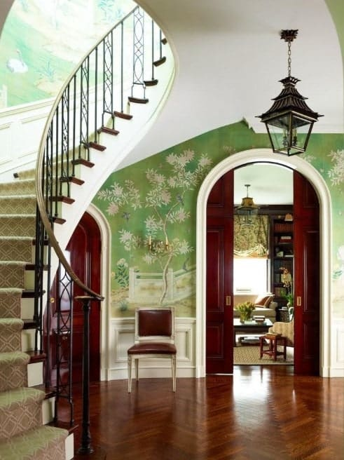This foyer features a magnificent flooring paired with beautiful green walls. The staircase looks lovely as well.