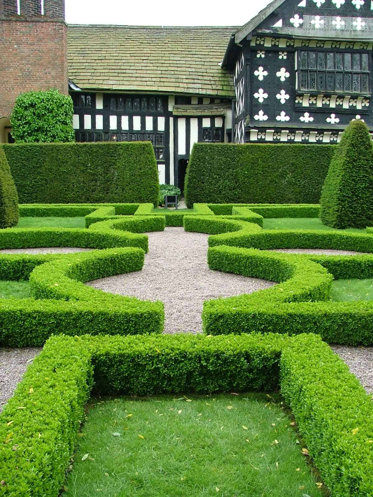 Hedge and knot garden outside Tudor revival house