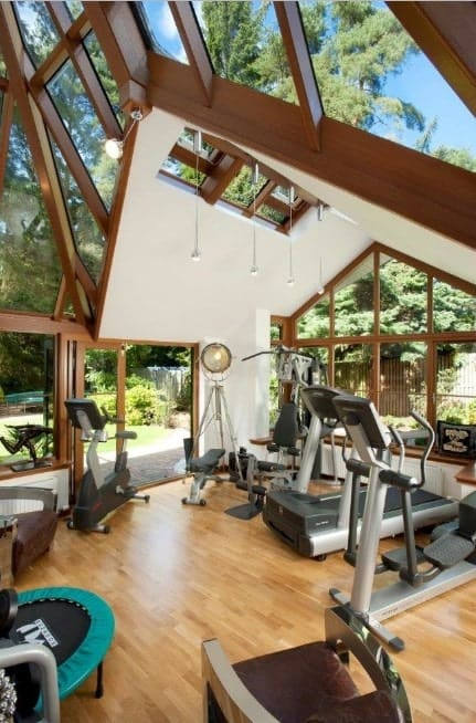 Using glass and wooden frames for the roof of your gym will let in a lot of natural light. It creates an inviting, open space to motivate you for the workout.