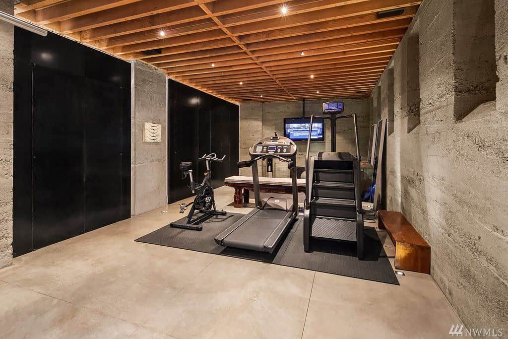 Modern home gyms use minimalistic equipment and wood paneling to make the space look better. Grey rustic walls also create an aesthetically pleasing home gym.