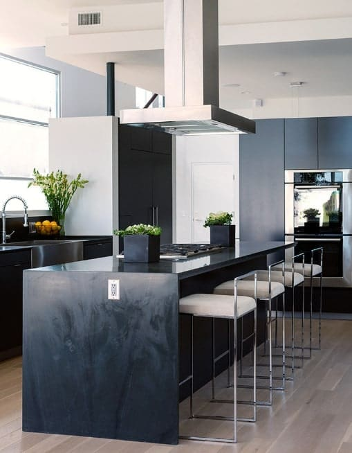 A black kitchen island topped with a cooking stove and potted plants also serve as a breakfast counter paired with stylish stools with chrome legs.