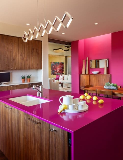 A kitchen island with hot pink countertop and wooden cabinetry matches the hot pink walls that face the wood dining set.