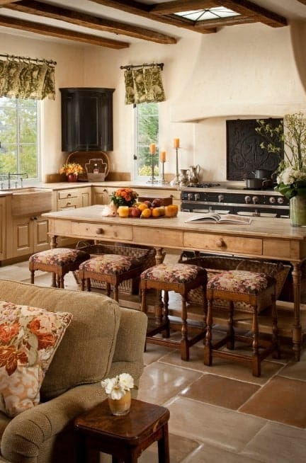 A wooden kitchen island with drawer is multifunctional in this Country kitchen with beam ceiling and tile flooring.