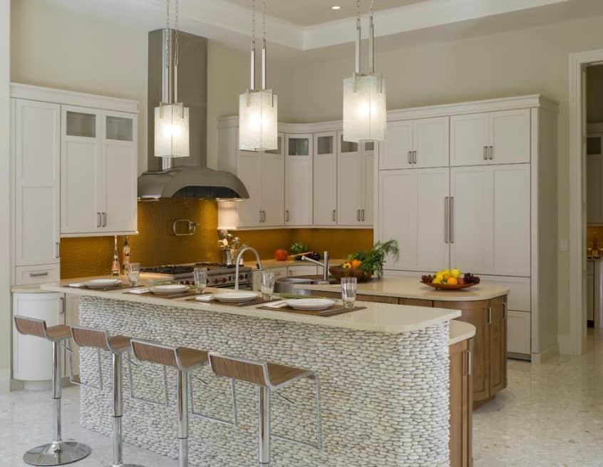 The two-tiered kitchen island features an unforgettable look with its stone base that faces the modern stools. The rest of the kitchen looks predictable with white cabinetry and a central island with wooden cabinetry.