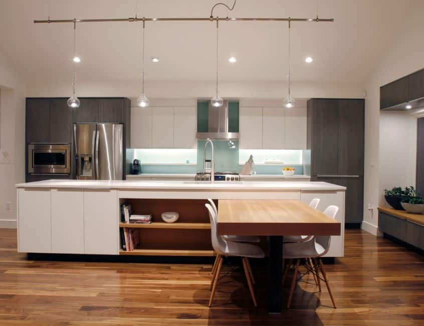 Stylish pendant lighting blends with this modern kitchen's stainless steel appliances and modern cabinetry. The kitchen island looks similar to the white upper cabinets but it also has open shelves for additional storage and an extended countertop for dining.
