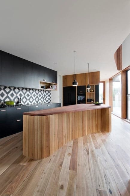 This contemporary kitchen features a custom-shaped kitchen island with wood countertop and a wooden base with lighter tones. Black cabinetry and its black-and-white backsplash add to the kitchen's modern look.