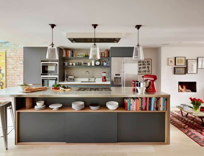 The large kitchen island with stainless steel countertop and gray base reflects the dominant theme of this Industrial kitchen. The island also serves as a cooking area, coffee station, breakfast counter, and even creates extra storage for dinnerware and books.
