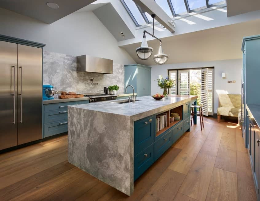 Skylights and shutter windows let in a stream of natural lighting to this dreamy galley kitchen. A large kitchen island encapsulates the look of the entire kitchen with marble countertop and side, green cabinetry with open shelves, and wooden breakfast counter.