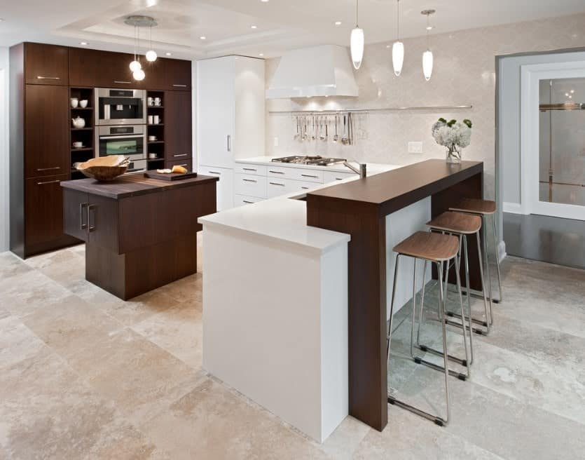 The two-tiered kitchen island copies the kitchen's colors in a nutshell. The crisp whiteness is offset with the warm tones of the central island and cabinetry with open shelving.