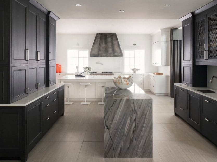 This U-shaped modern kitchen has two kitchen islands but the one that really captures the eye is the one made of gorgeous marble and flanked by a galley of black cabinetry.