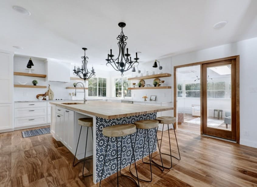 The kitchen island's decorative base underneath the wooden countertop captures attention in this Farmhouse kitchen. Black candelabra chandelier create focal points in the white kitchen canvas with wooden ledges for storage.
