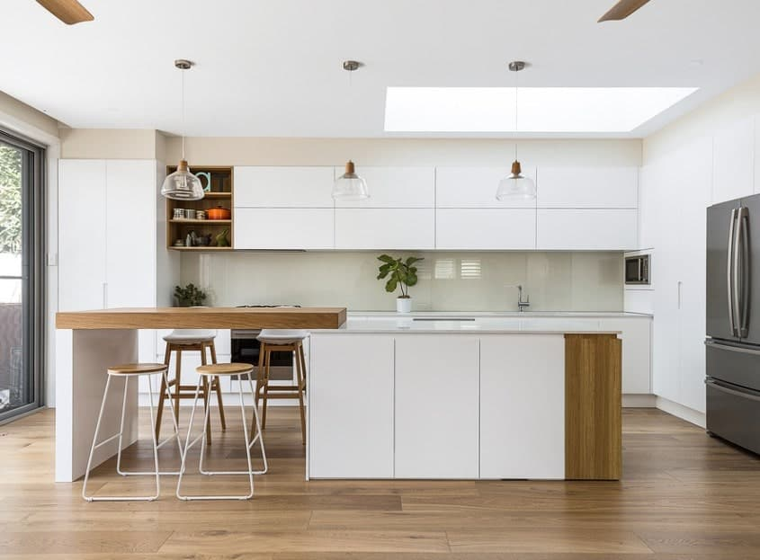 This minimalist kitchen features the kitchen island with a wooden block as the breakfast counter.