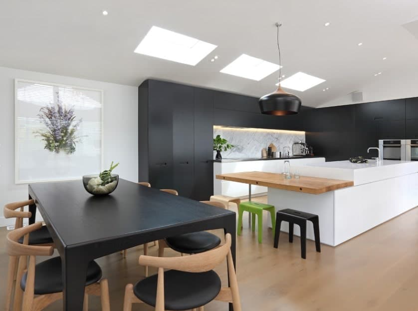 A large white kitchen island with an extended wooden countertop for breakfast counter offsets the minimalist kitchen's black cabinetry and dining set.