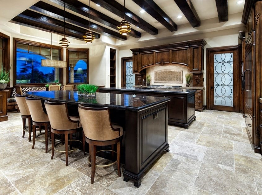 A pair of large kitchen islands reflects the dark wood tones of the beam ceiling above while complementing the surrounding wooden cabinetry. Each island serves a purpose: one for serving breakfast and the other for cleaning up after.