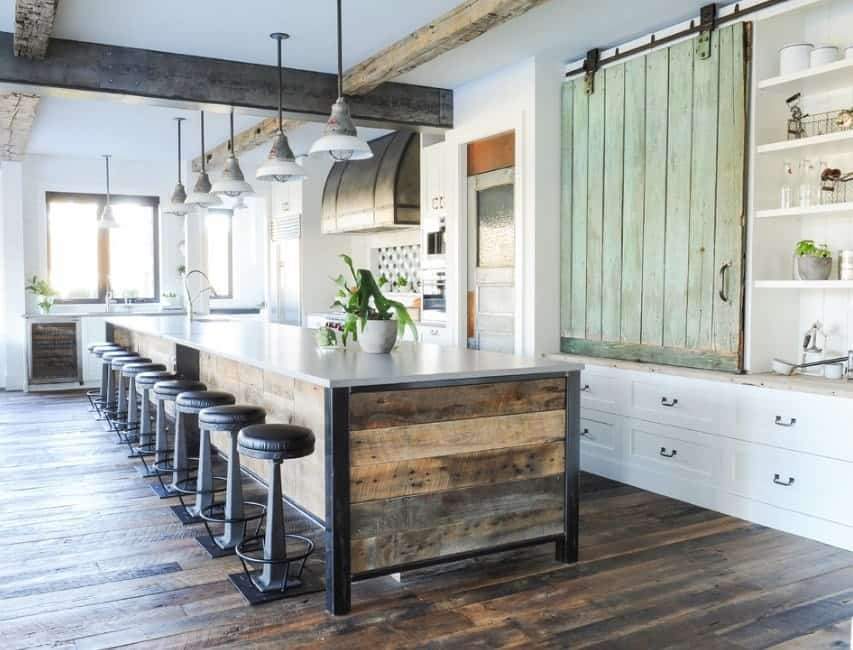 This gorgeous kitchen offers plenty of focal points from the wooden and steel beams to the green barn-style sliding cabinet door. It also features the long kitchen island with wooden pallets and steel legs that matches both the line of vintage pendant lighting above and the wooden flooring underneath.