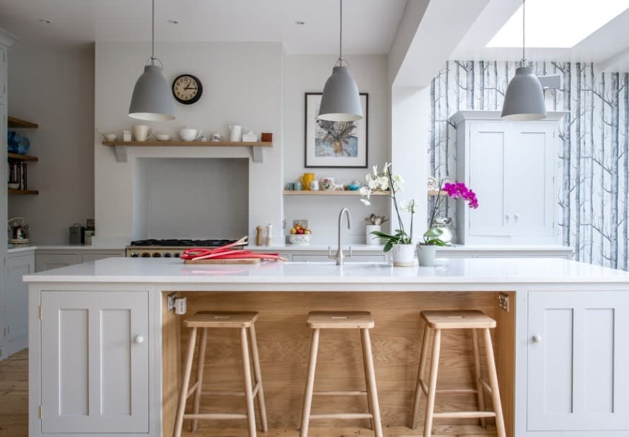 A trio of pendant lights direct attention to the white kitchen island underneath. The island has cabinetry on both sides and a carved space for storing the bar stools underneath.
