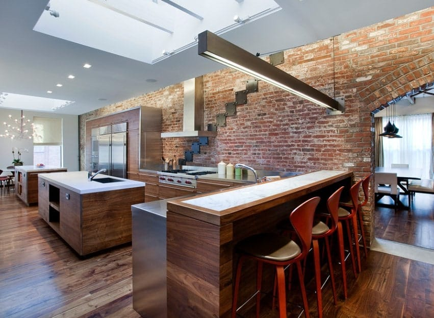 This single wall Industrial-style kitchen with skylight, fluorescent lighting, exposed brick walls, stainless steel countertop, and wooden cabinetry features double kitchen islands and a two-tiered island.