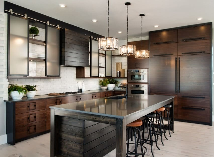 This trendy kitchen with handsome wooden cabinetry features glass cabinet doors and a dark-toned kitchen island with steel countertop.