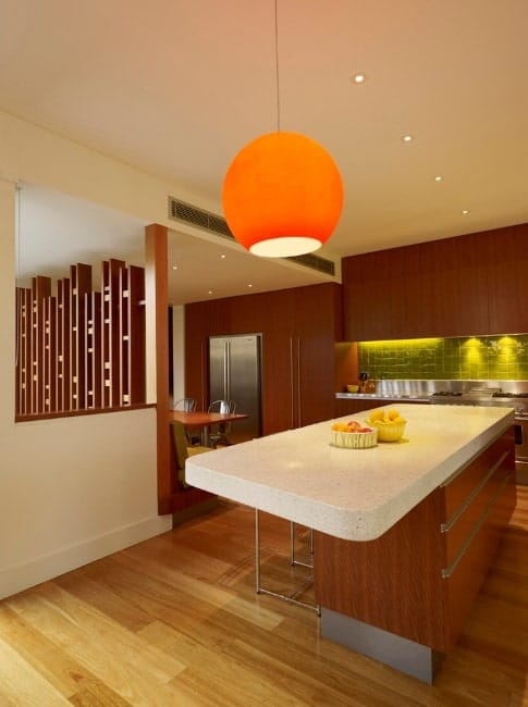 The orange pendant lighting above the kitchen island looks like a rising sun. The wooden cabinetry also has ambient lighting to feature its tile backsplash.