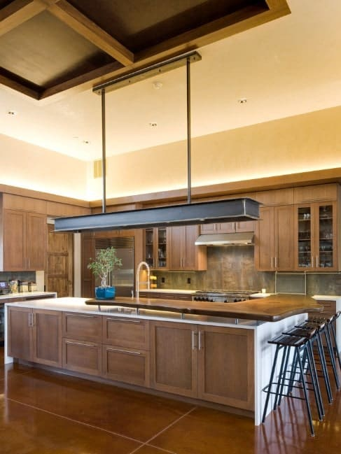 Large fluorescent lighting directs attention to the L-shaped two-tiered kitchen island with a polished custom-shaped wooden block for its breakfast counter.