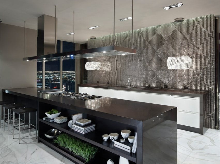 This luxurious galley kitchen features an overlooking view of the city skyline as well as a glimmering backsplash over the sink and a black kitchen island that serves as a cooking area, breakfast counter, and extra storage space.