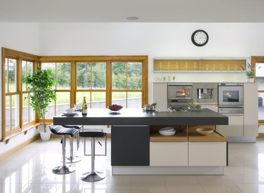 This simple kitchen features an inviting view of the green outdoors framed by its wooden windows and a kitchen island with a gray countertop that serves as a breakfast counter and a cooking area.