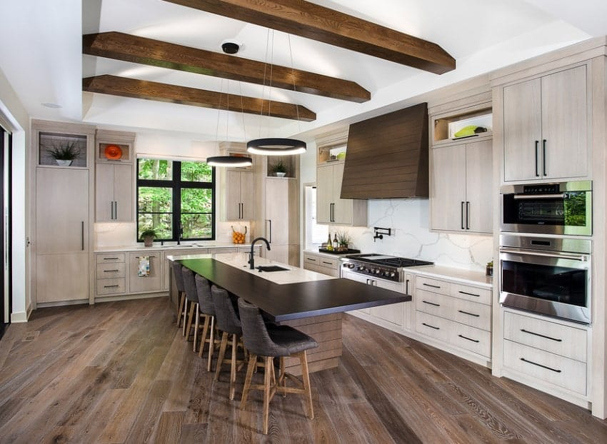 This kitchen has beam ceilings and stylish lighting above the modern L-shaped kitchen island. The white part of the island's countertop serves as a working area for washing while the wooden part serves as the breakfast counter.