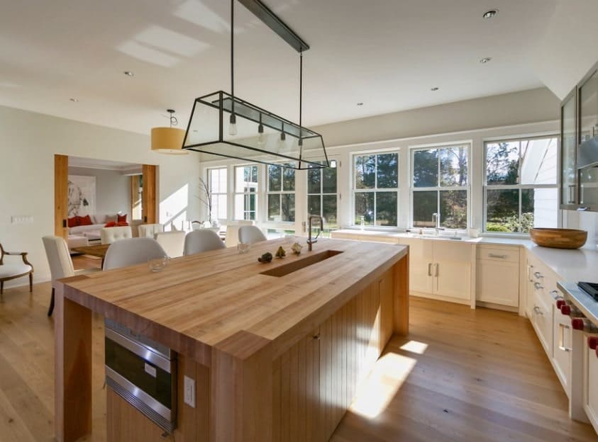 A wooden kitchen island with sink and breakfast counter makes the all-white kitchen look warm and cozy.