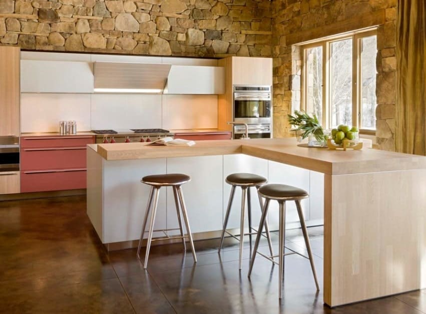 An L-shaped wooden breakfast counter is attached to a modern white kitchen island topped with sink. The entire kitchen itself is equally unique as the modern kitchen is completely surrounded by stone walls.