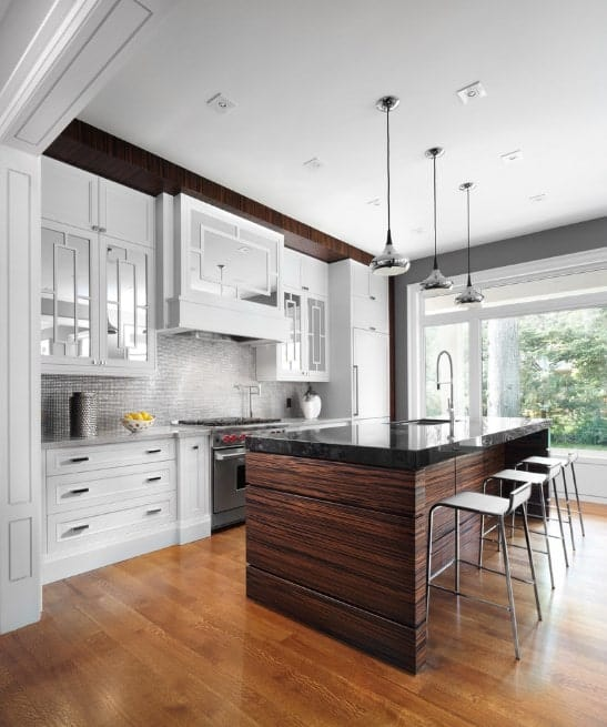 A dark kitchen island with black marble countertop and a dark-toned wooden base injects a jolt of visual warmth to the crisp whiteness of the kitchen with stainless steel backsplash and glass cabinet doors.