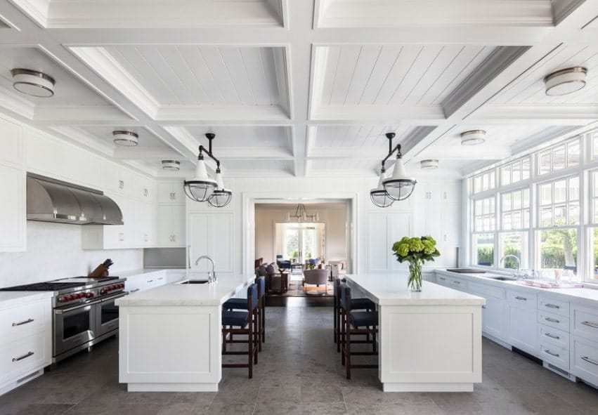 Coffered beam ceiling with flush mount lighting and Industrial lights draw the eyes upward in this large Farmhouse galley kitchen. Large double kitchen islands with blue chairs are just the perfect sizes for this large and breezy kitchen.