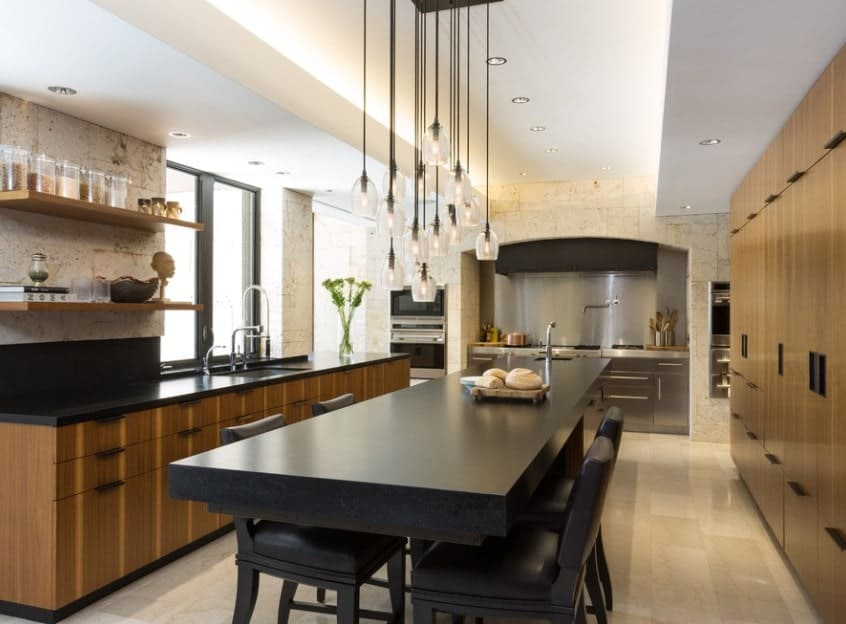 A bunch of Industrial pendant lights and a galley of modern wood cabinetry draws attention to the long and rectangular kitchen island with a black countertop. One end serves as the breakfast counter for four while the other is topped with a sink and faces the U-shaped kitchen's cooking area.